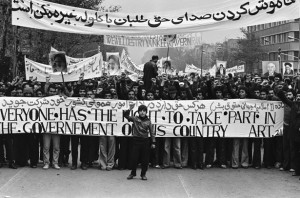 """An Iranian boy, fist raised in symbolic defiance, heads a huge crowd of Ayatollah Khomeini supporters across Tehran in an anti-Shah demonstration estimated at over a million strong, Dec. 10, 1978. Behind him demonstrators carry a banner reading: """"Everyone has the right to take part in the government of his own country,"""" and behind another reads: """"We will destroy Yankee power in Iran."""" (AP Photo)"""